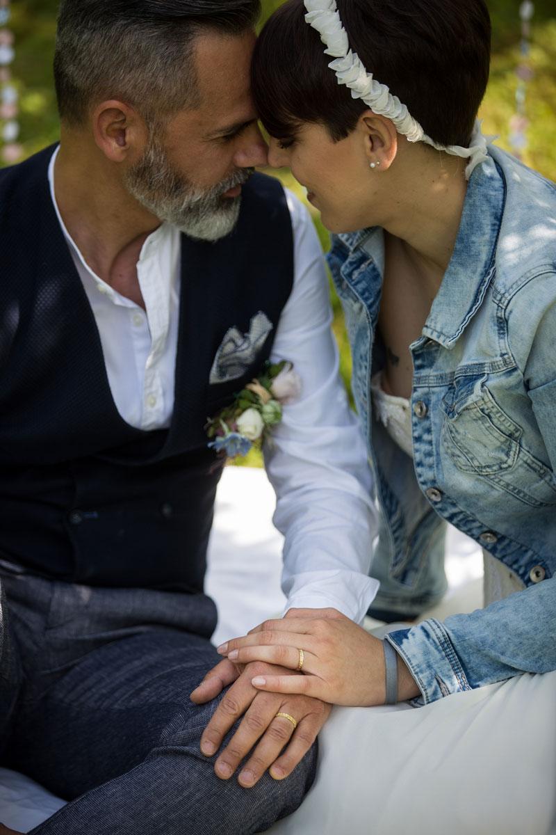 coppia sposi con mani intrecciata e fedi