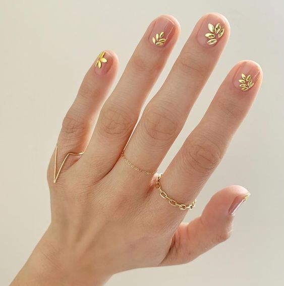 manicure nude con foglioline dorate