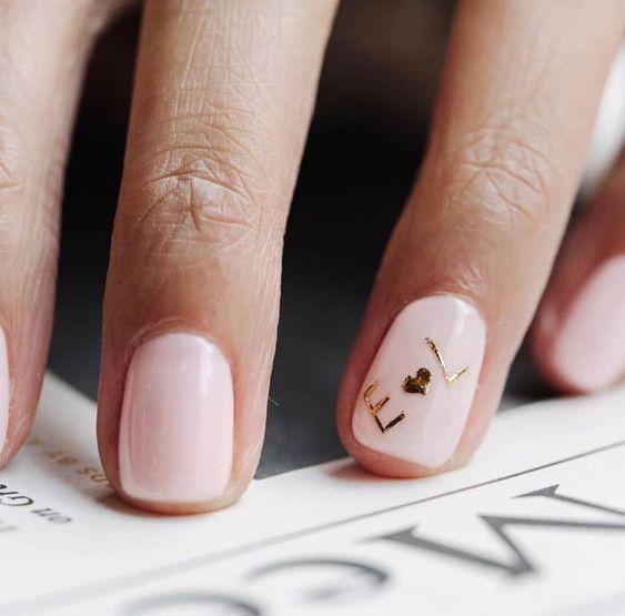 manicure rosa con iniziali dorate
